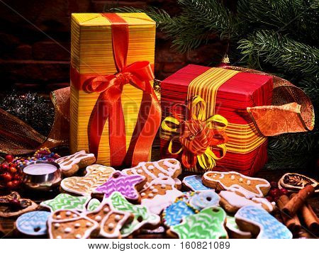 Christmas gingerbread cookies for decoration under Christmas tree with gifts box.