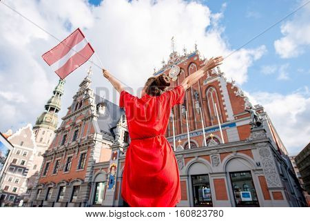 Young female tourist with latvian flag on the main old town square in Riga. Woman having great vacations in Latvia