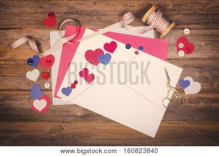 A vintage scrapbooking themed background with cutout hearts, craft paper, ribbon and buttons. Space for your text. Filtered to look like an old photo, nostalgic style.