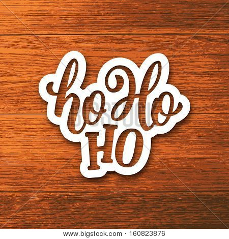 Ho-ho-ho text on white paper label with hand lettering over wooden background. Vector sticker design for Christmas and New Year decoration