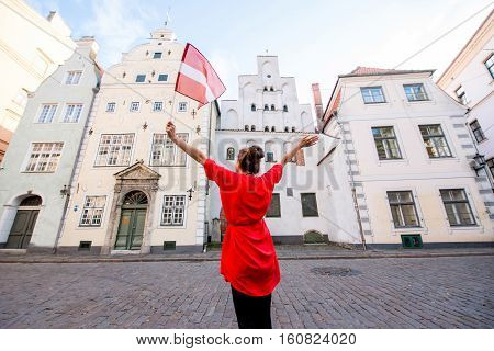 Portrait of a young female tourist with latvian flag in front of the famous three brothers ancient houses in Riga. Woman having great vacations in Latvia
