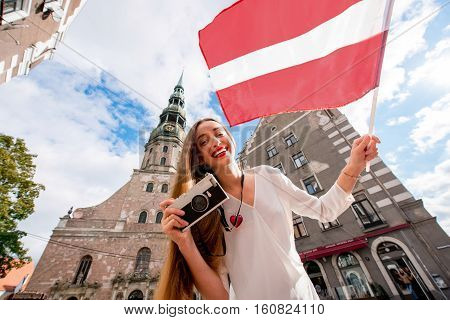Portrait of a young female tourist with latvian flag in front of saint Peter church in Riga. Woman having great vacations in Latvia
