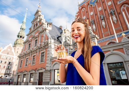 Young woman eating Riga's sprats in the old town square in Latvia. Riga is famous for it's tasty golden and smoked fish called sprats. poster