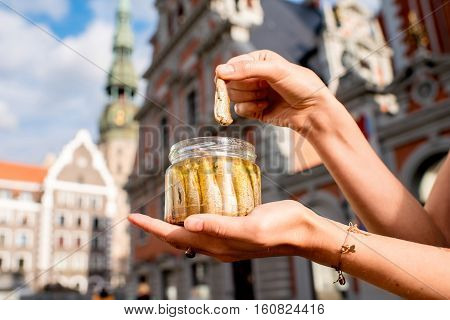 Female hands holding a jar with sprats in the center of Riga city. Riga is famous for it's tasty golden and smoked fish called sprats.