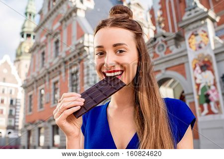 Young female tourist with chocolate bar in the old town of Riga city in Latvia. Riga is famous for it's chocolate producing