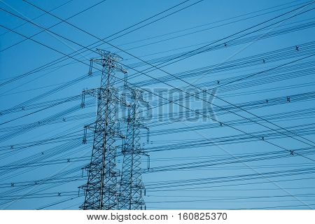 horizontal shot of High-voltage towers silhouetted against blue sky