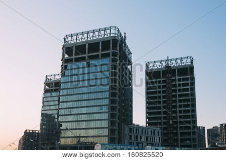 low angle of unfinished building on a background of blue sky at sunset time.