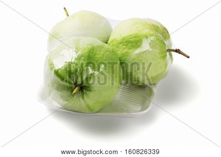 Three Guava Fruits in Cellophane Wrap on White Background (Psidium guajava)