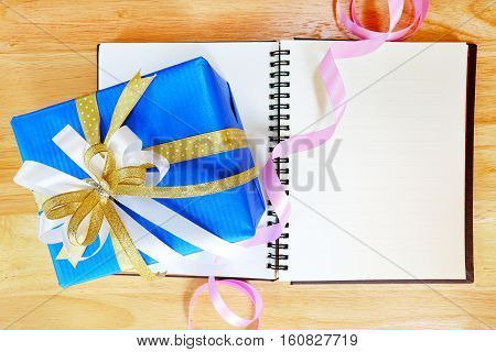 Gift box and colorful of ribbon on wood background.