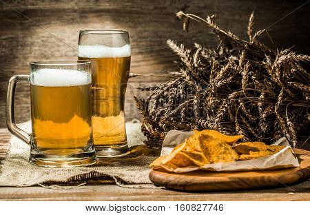 Beer in mug, glass on wooden table with wheat spikelets and potato chips on eth board