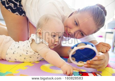 Happy and caring mother laughing together with her child. Smiling and cute young baby girl playing on mat.