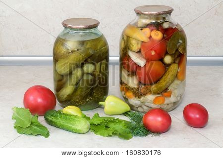 Home canning: large glass cylinders with a variety of vegetables: cabbage tomatoes cucumbers peppers. Sealed with metal caps. Located next to fresh vegetables.