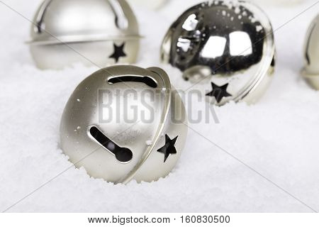 Gold Christmas baubles in the snow with de-focused background and shallow depth of field. Space for text.