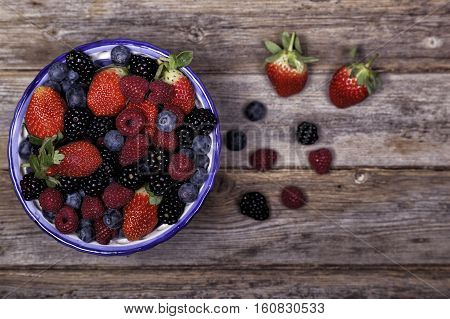 Mixed ripe sweet berries in a blue and white bowl with some berries that have spilt out of the bowl blurred focus on a wooden backgrouond. Blueberries raspberries strawberries and blackberries. With space for text.