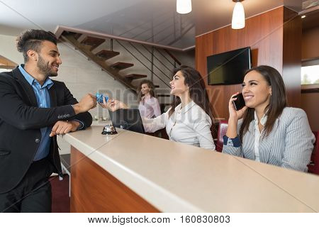 Business Man Arriving To Hotel Give Meeting Woman Receptionist Credit Card Pay Room Registration At Reception Counter Checking In