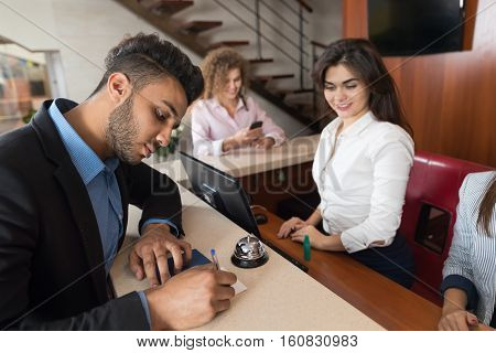 Business Man Arriving To Hotel Singing Document Meeting Woman Receptionist Room Registration At Reception Counter Checking In
