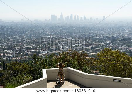 Los Angeles USA - September 27 2015: Girl looks through binoculars at the downtown Los Angeles