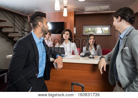 Two Business Man Arrive To Hotel Check In Woman Receptionist Registration At Reception Counter