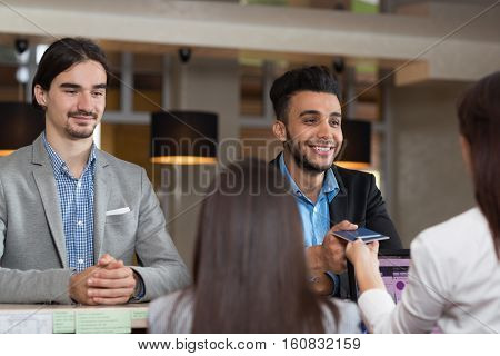 Two Business Man Arriving To Hotel Give Passport Meeting Woman Receptionist Room Registration At Reception Counter Checking In