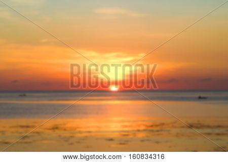 Beautiful orange sunset by seaside blurred photo. Sunset sky and ocean landscape in blur. Retro style blurry image of tropical sunset. Summer vacation travel card or banner template. Blurred sea view