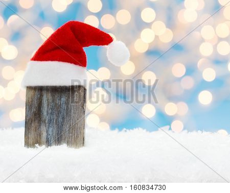 Wooden board with Christmas hat in the snow