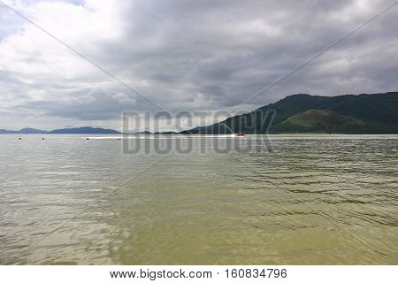 Sea greenish colors, soft rippling water, clear water, mountains on the horizon, the sky with clouds, in the distance a man riding a water bike