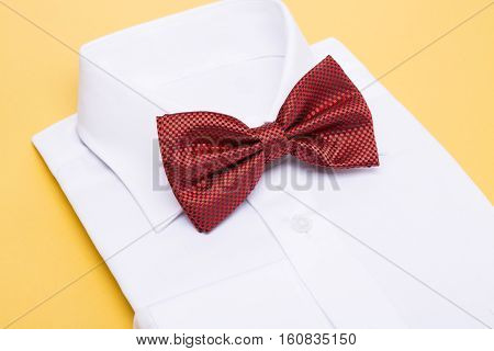 Red bow tie on a white shirt, yellow background