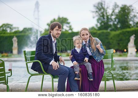 Happy Family Of Three In The Garden Of Palais Royal In Paris