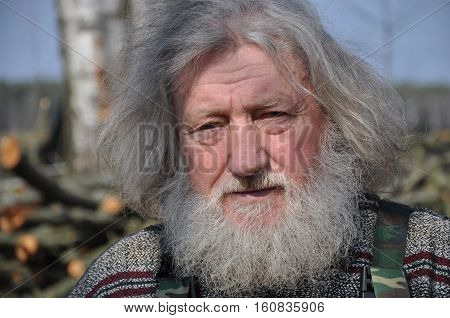 GRODNO, BELARUS - MARCH 27, 2016: The resident of the Belarusian village. Portrait of an old man with long gray disheveled hair and beard.