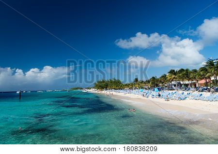 Grand Turk Grand Turk and Caicos Island - December 29 2015: tropical resort beach or coast with white sand green palms beautiful turquoise waters of sea or ocean on sunny day on blue sky