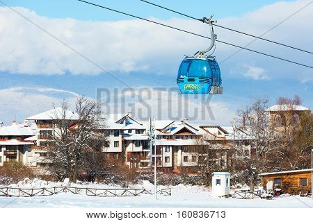 Bansko, Bulgaria - November 30, 2016: Ski resort Bansko, Bulgaria panorama with cable car ski lift cabin, snow mountains and houses in winter