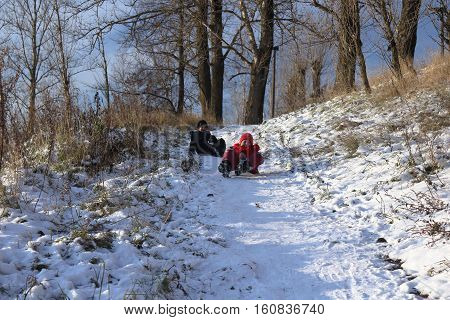 Beautiful winter day. Fun, Kids Games. Snow on the bank of the river. Trees under the snow. The low winter sun.