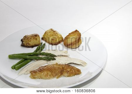 Chicken dinner with asparagus and roast potatoes. Small healthy cafeteria meal prepared for a calorie controlled diet without sacrificing taste.