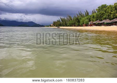 beautiful views of the sea of Vietnam, greenish sea water, shooting out of the water, mountains on the horizon, the cloudy sky, the clouds, the fog over the mountains, a piece of yellow beach with green trees