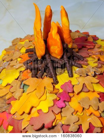 This image features detail from a wedding cake designed to fit the themes of autumn and bonfire night in the UK. The leaves are made by combining different coloured icing in various combinations. The bonfire combined chocolate twig like sticks and flames