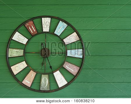 Old vintage clock on green wooden wall