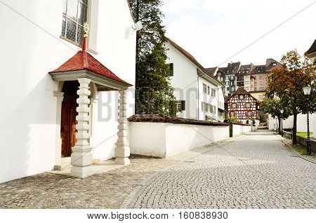 Church and characteristic cobblestone road in Bremgarten Aargau Switzerland