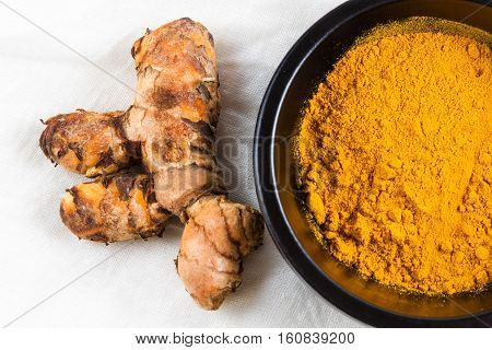Turmeric Root With Bowl Of Powder On White Cloth Background