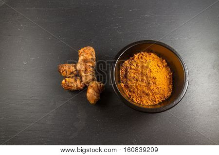 Turmeric Root With Bowl Of Powder On Dark Slate Background