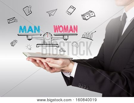 Equality of man and woman. Young man holding a tablet computer