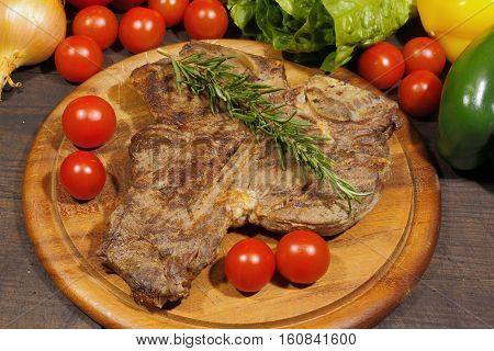 Grilled T bone steak with rosemary tomatoes onions and pepper garnished on a rustic wooden chopping board