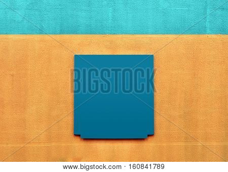 Architectural background. Orange stucco wall with blue stripe on top. The gray metal empty notice board in the middle.