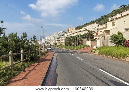 Asphalt Road And Beachfront Buildings And Blue Cloudy Skyline