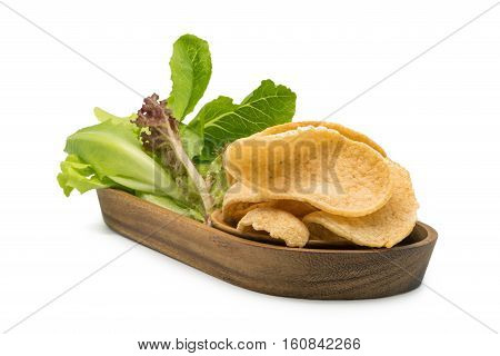 Crunchy prawn cracker and vegetables in a wooden tray on white background