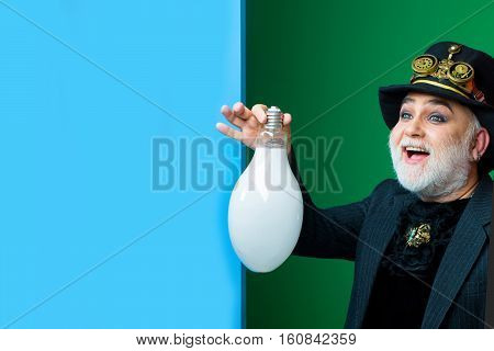 Smiling senior bearded man or watchmaker with white beard in black hat with watch mechanical metallic gears and cogwheels holds light bulb on green blue wall copy space