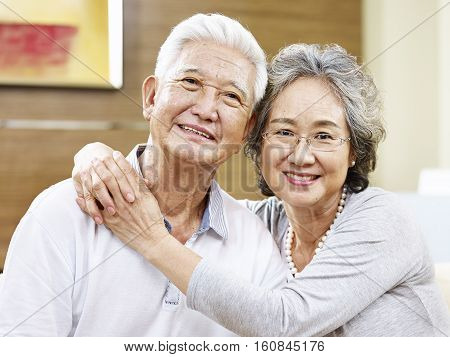 portrait of a loving asian couple looking at camera smiling