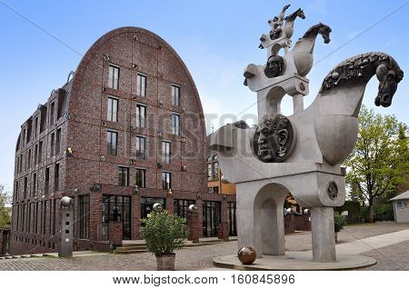 Bietigheim, Germany - April 19, 2016: Street modern sculpture of horses facing each other and round facade of Visconti villa decorated with sculptures of heads.