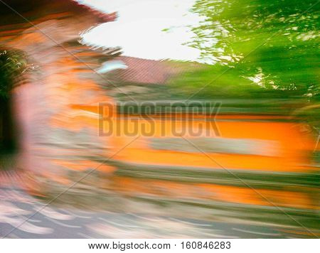 Abstract blur background of traditional Balinese architecture by motorbike. Fast driving bike roadside view. Speed blur photo of Bali island. Stone gate and wall defocused image. Fast tourism concept