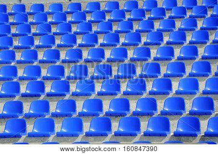 empty plastic blue seats on football stadium