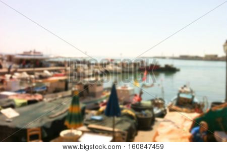 Sea view in European town. Italian coastal city blurred photo. Beach umbrellas and chairs by the sea. Summer town in Italy blurry image for background or postcard. Vintage seaside picture in blur